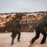 Após desembarque de bote, elementos do Corpo de Fuzileiros Portugueses assaltam uma praia. Estão armados de Metralhadora ligeira Mg3, Espingarda Automática G3 e Pistola P38.