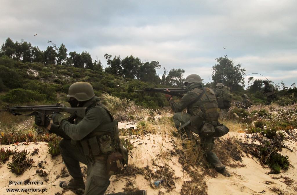 Após sofrerem uma emboscada enquanto patrulhavam um rio, estes Fuzileiros assaltam a praia de modo a eliminarem a ameaça. Estão armados de Espingarda Automática G3 e Pistola P38.