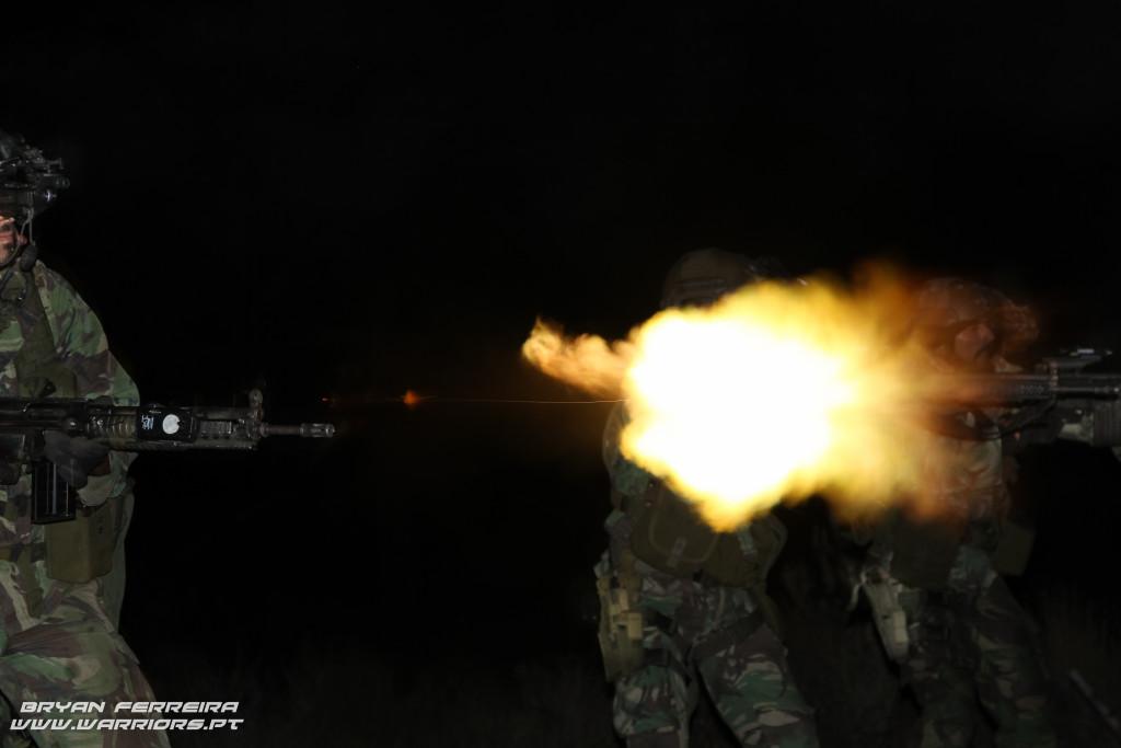 Elementos do pelotão reconhecimento fazem fogo nocturno. Estão equipados com visores nocturnos (NVG) no capacete e apontadores laser (AN/PEQ) nas armas