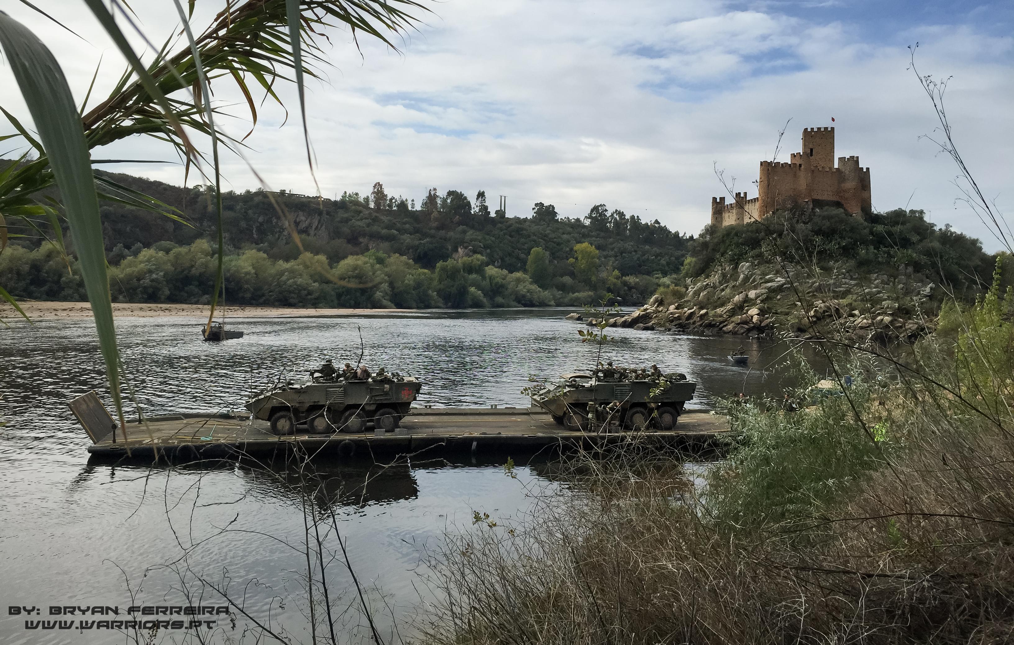 Duas PANDUR APC atravessam o Rio Tejo usando pontes flutoantes Portuguesas. Podemos ver o Castelo de Almourol ao fundo.