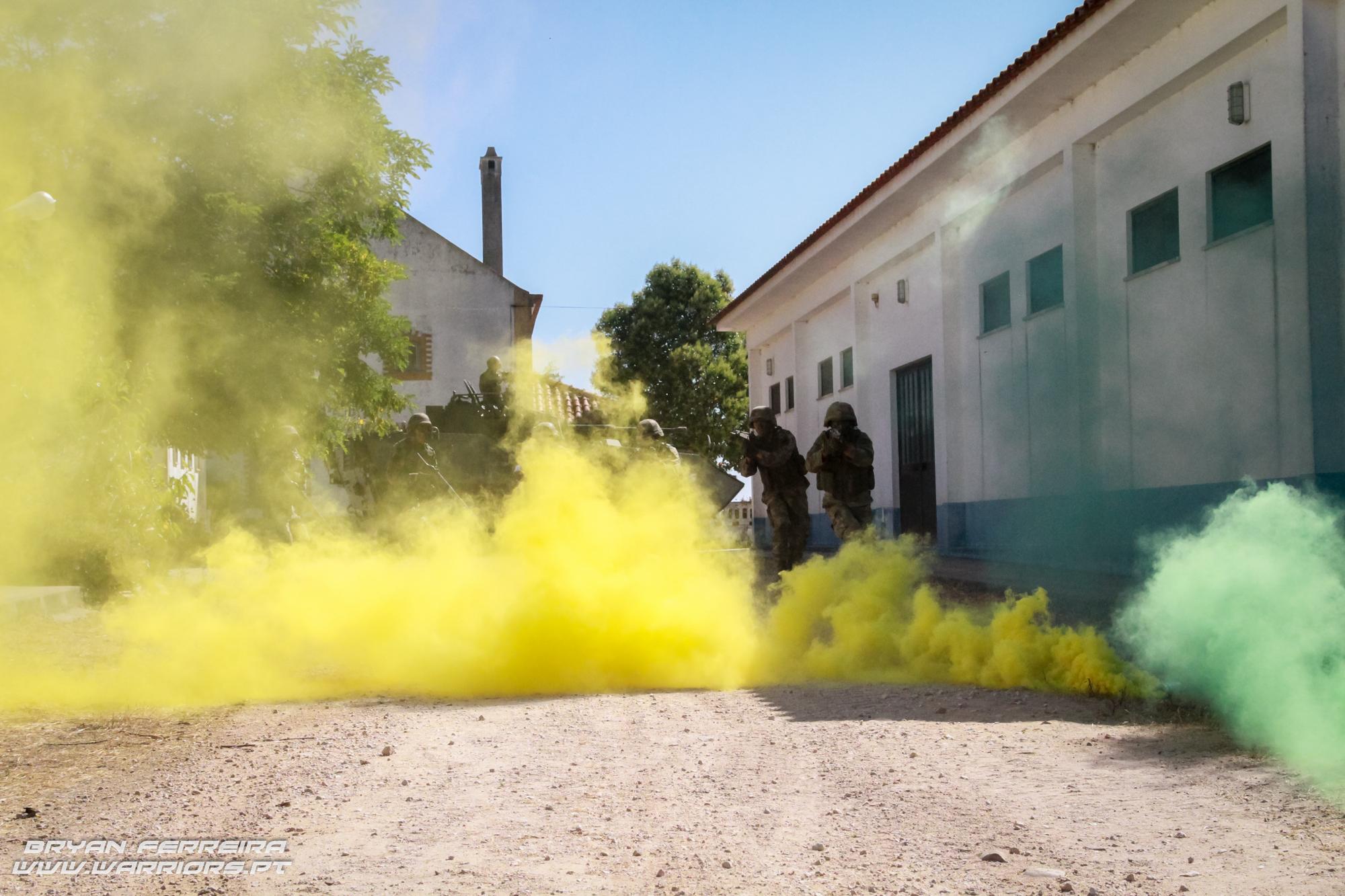 Infantaria da Brigada de Intervenção desloca-se numa Área Urbanizada, sob a cobertura de uma cortina de fumos, de modo a limpar quaisquer ameaças às viaturas pesadas.
