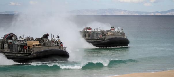 2 LCAC da US Navy voam até à praia de modo a desembarcar HMMWV e LAV25 dos US MArines