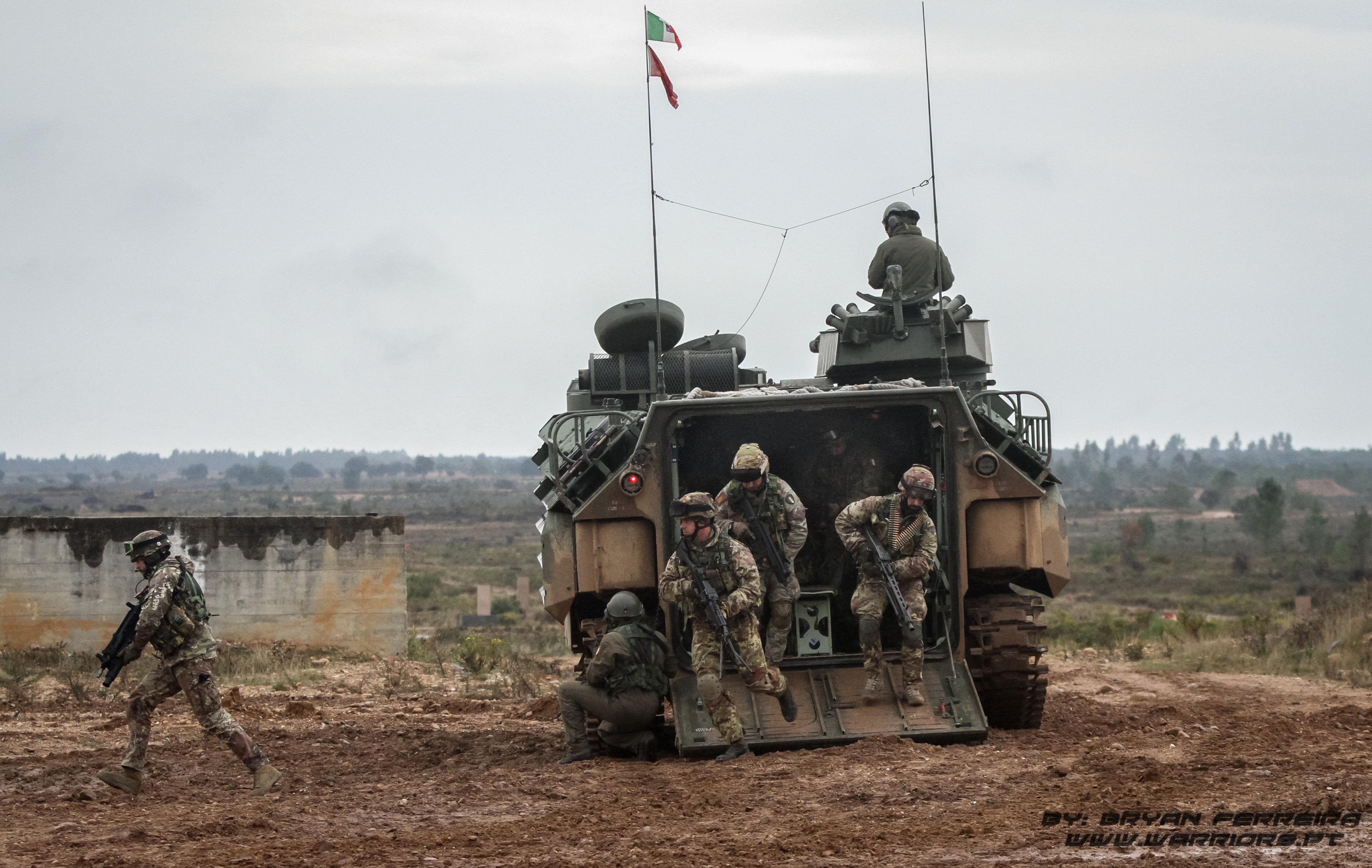 Soldados Italianos do Reggimento Lagunari desembarcam de um dos seus Blindados anfíbios, AAV7. Estão equipados de espingardas de assalto ARX160, Lança Granadas GLX 160, e metralhadoras Minimi e Mg3